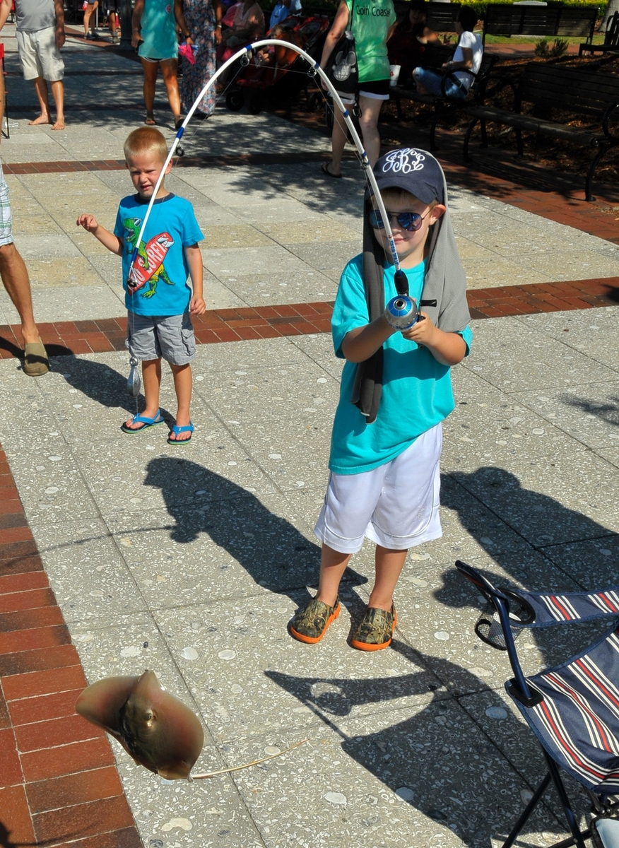 """Kason Jenkins, 6, catches """"a big stingray"""" from the sea wall during the Water Festival Children's Toad Fish Tournament on July 15."""
