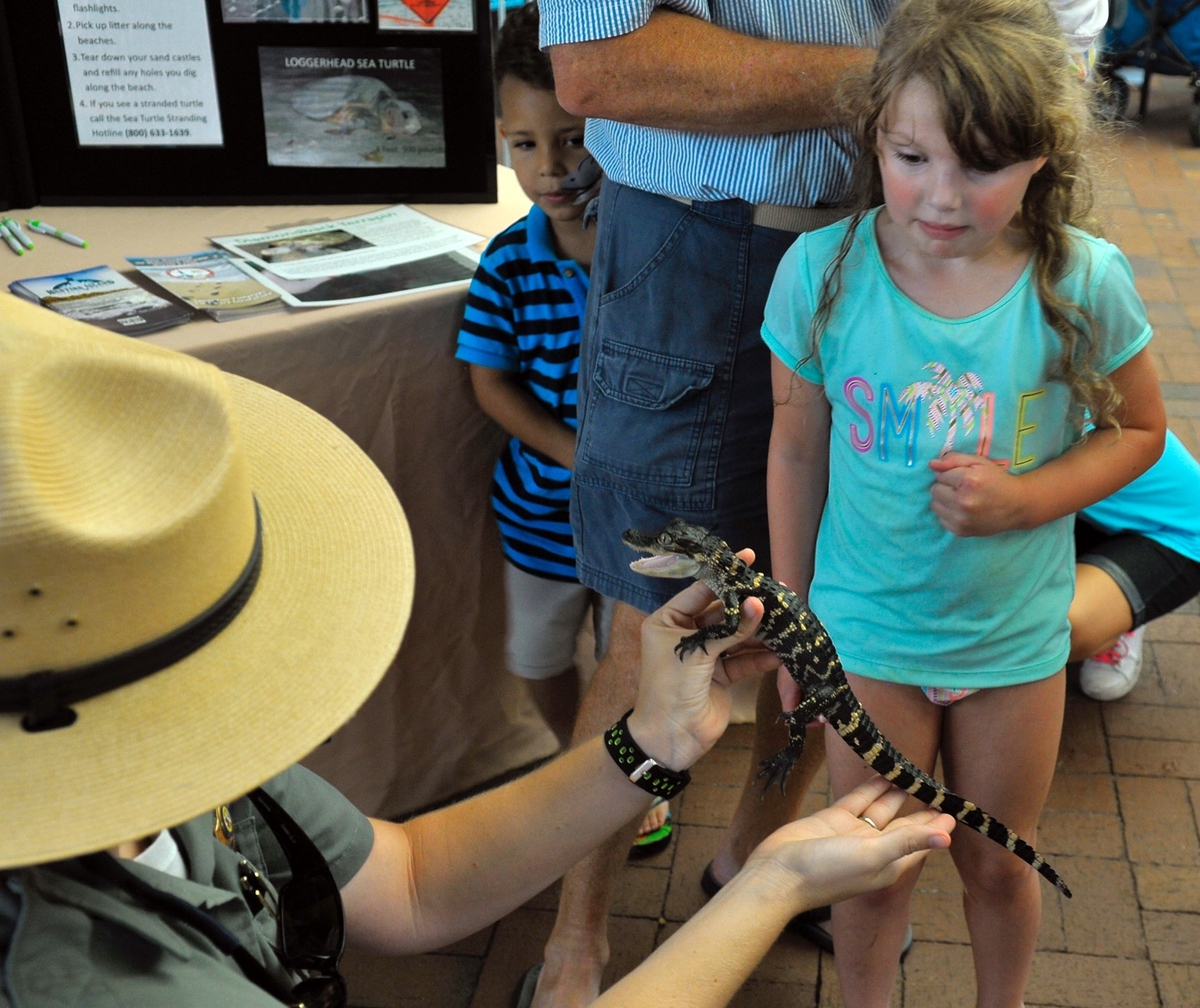 Ranger Megan Stegmeir, left, of Hunting Island State Park, holds a 3-year-old American alligator for children to touch on Children's Day at the Beaufort Water Festival. Stegmeir said the gator is small because captivity seems to stunt their growth. The child in the background was reluctant to even get close to it.