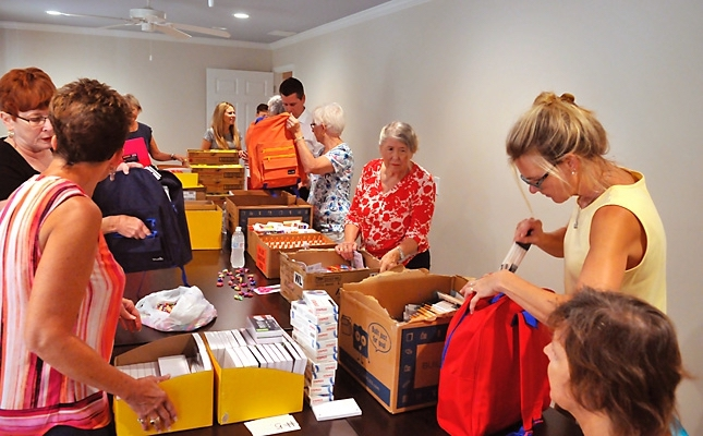 "Children from throughout Beaufort County started school on Aug. 17, and many of them got some help to kick off the year with new school supplies. Here, about a dozen volunteers help fill new back to school backpacks with all kinds of school supplies donated by area businesses, individuals and a few gated communities during Operation Back Pack recently at United Way office on Ribaut Road. ""We're filling 600 back packs destined for eight schools in Beaufort and Jasper counties,"" said Jaime Dailey-Vergara of the United Way. ""We're working through school counselors to assist in identifying students in need not currently being served by any other agencies."" Photo by Bob Sofaly."