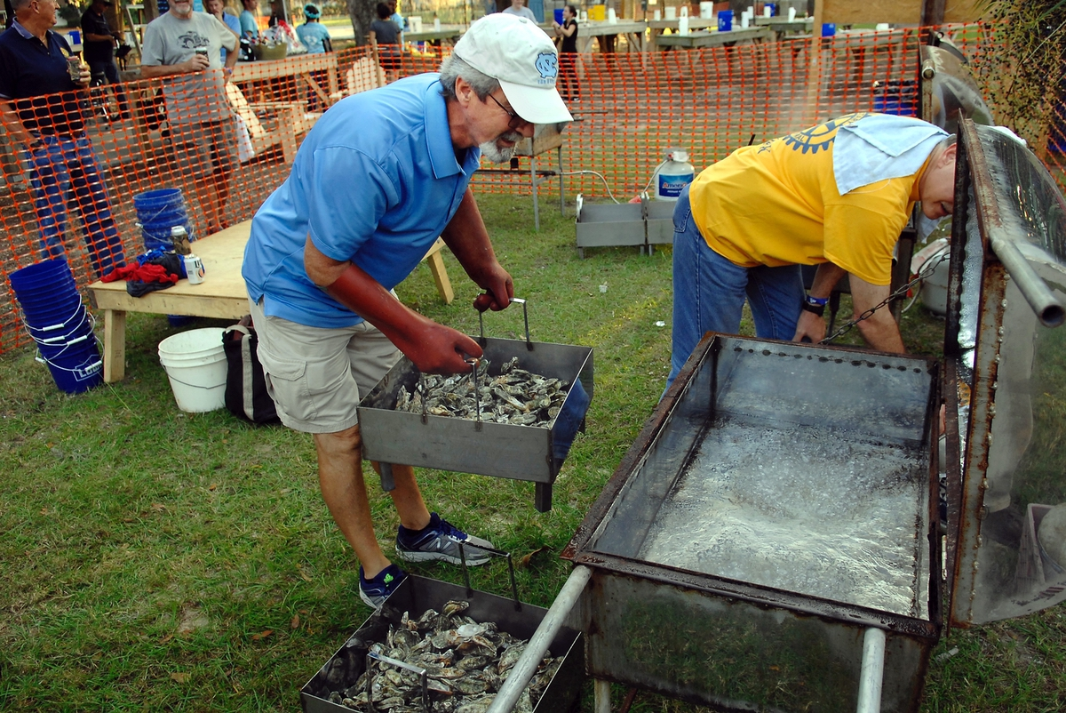 Kerry Bunton, left, of the Rotary Club of the Lowcountry, loads some of the 75 bushels of fresh oysters into a steamer to kick off the 21st annual Family Oyster Roast in Port Royal. At right, fellow Rotarian Andy Thacker adjusts the heat.