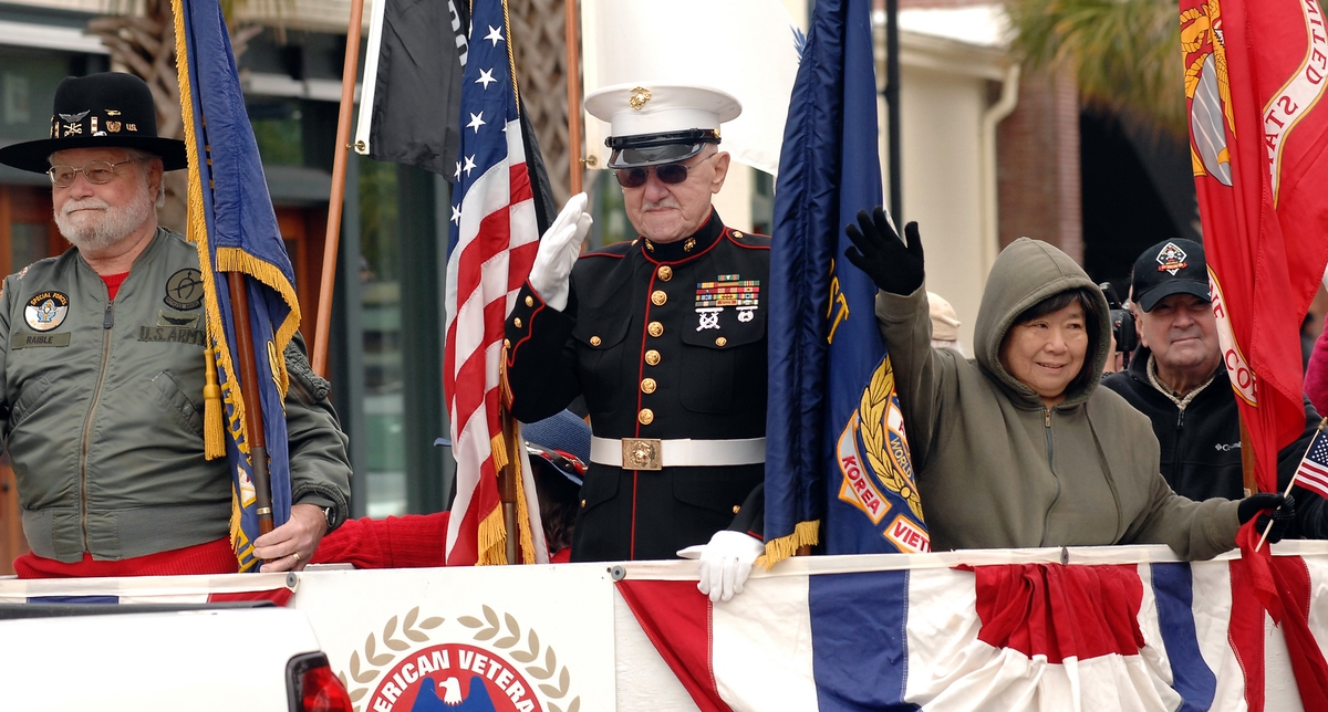 Retired Marine Corps Master Sgt. James Handrinos, center, stands front and center on the American Legion float makes its ways down Carteret Street during the annual Veterans Day Parade.
