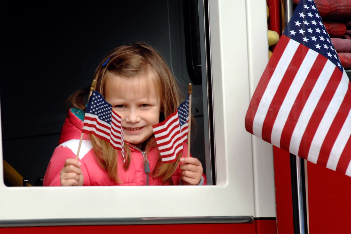 Emily Kelly waves to the crowd during the annual Veterans Day Parade. Emily's dad, firefighter Keith Kelly, was driving a fire truck in the parade.
