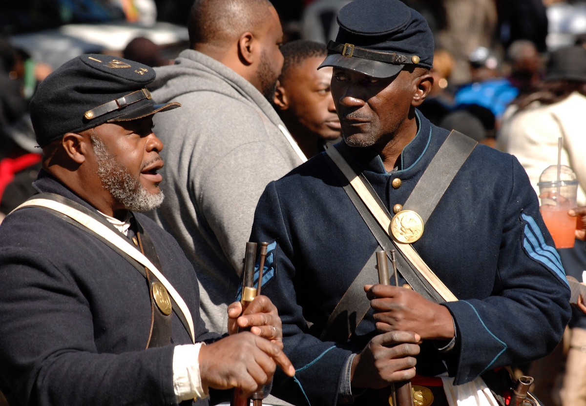 Pvt. Terry James, left, portraying a soldier of the 54th Massachusetts, and Sgt. Gilbert Walker, of the First South Carolina, walked around Penn Center grounds and gave a living history as they answered questions about what it was like being a black Union soldier during the Civil War.