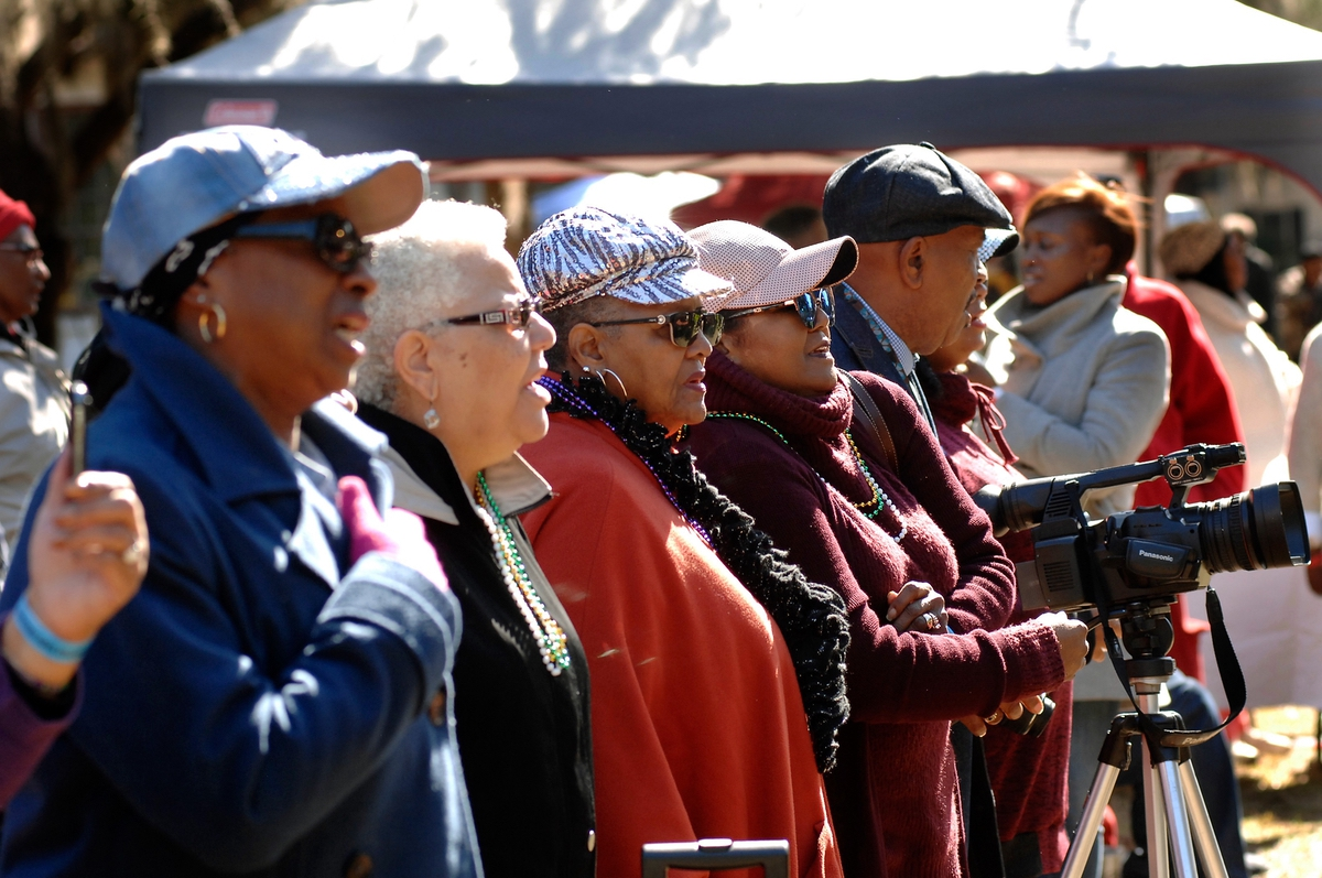 "Attendees of the annual Heritage Days celebration stand and sing ""Lift Every Voice and Sing."" The song, also referred to as the ""Black National Anthem,"" was written as a poem by James Weldon Johnson in 1900 and later set to music in 1905."