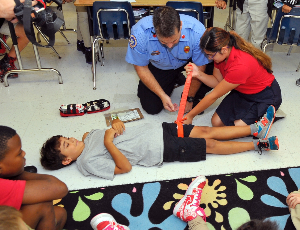 Hannah Boyd applies a tourniquet and locks it down with Velcro as Lt. Daniel Byrne of the Burton Fire District looks on. The demonstration at Port Royal Elementary School was intended to show the simplicity of using Jacob Kits. Photo by Bob Sofaly.