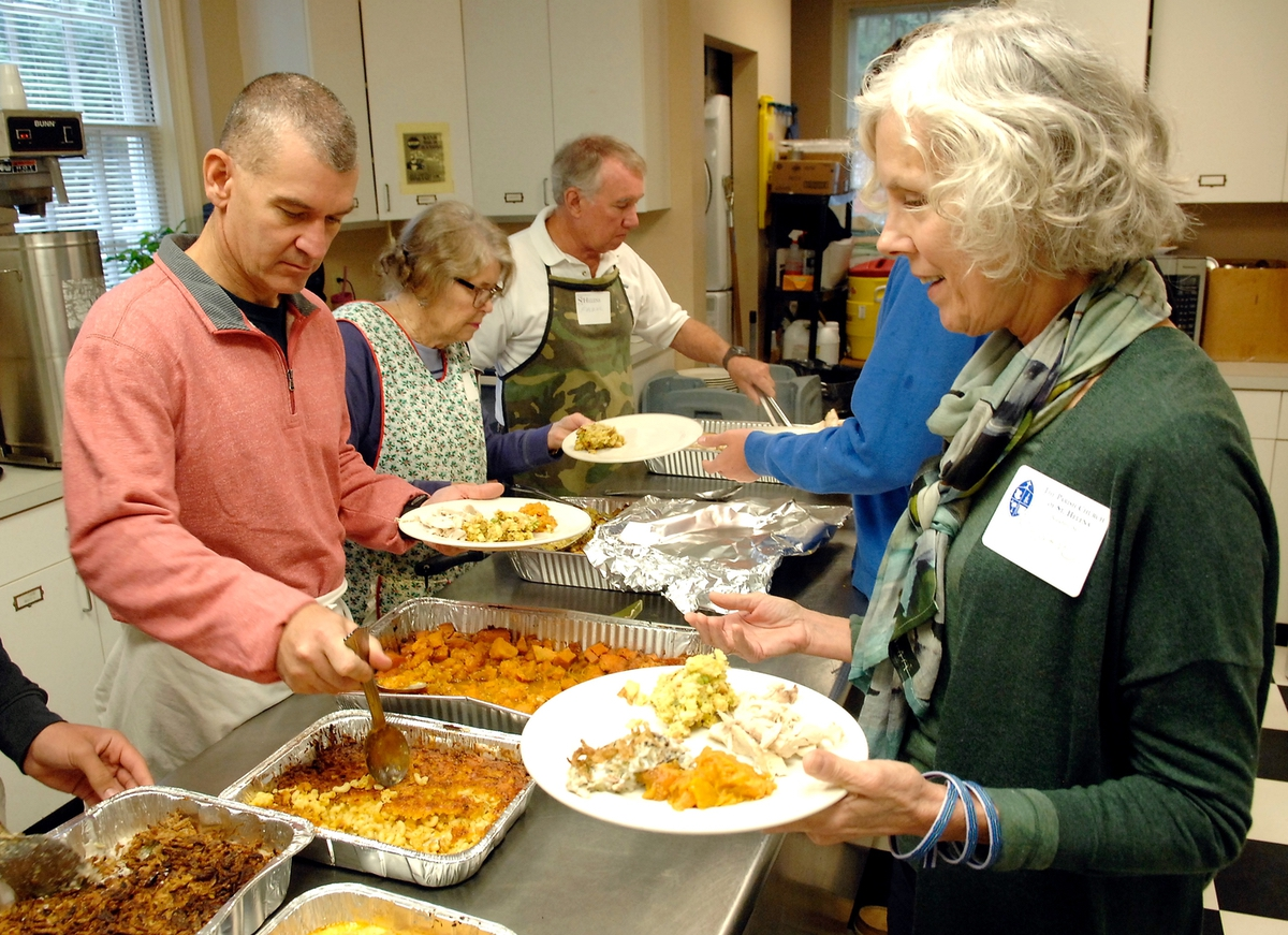Sharon Reilly, right, gathers traditional Thanksgiving meals and brings them to the table at St. Helena Episcopal Church.