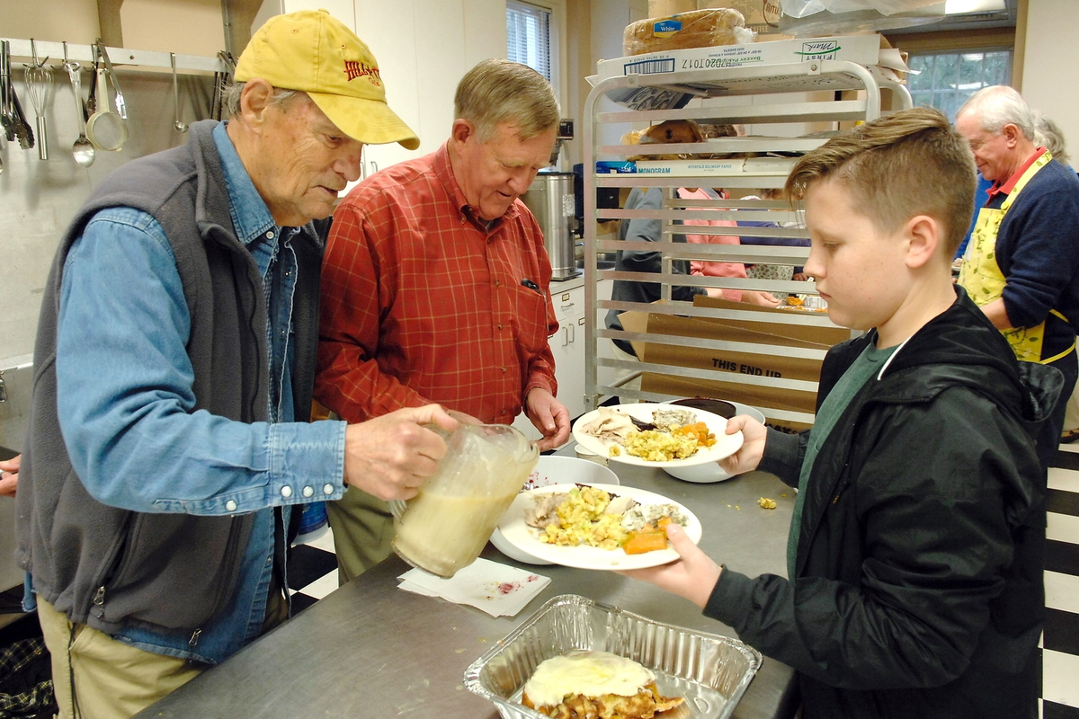 Larry Hynson, left, and Jack Klimpman work as Thomas Milam moves down an assembly line of Thanksgiving food at St. Helena Episcopal Church.