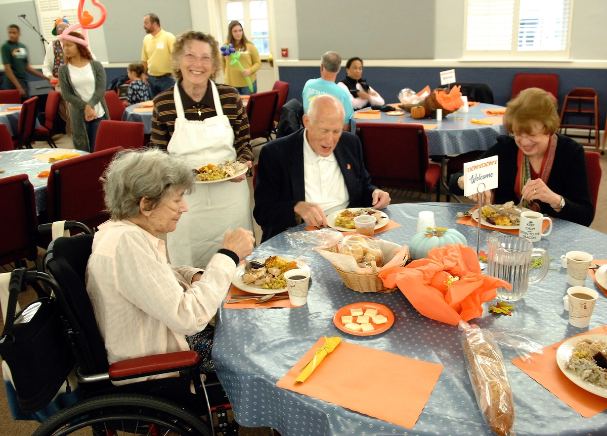 """Patrons are seated at tables after which volunteers come and take their """"order"""" and deliver Thanksgiving meals at St. Helena Episcopal Church."""
