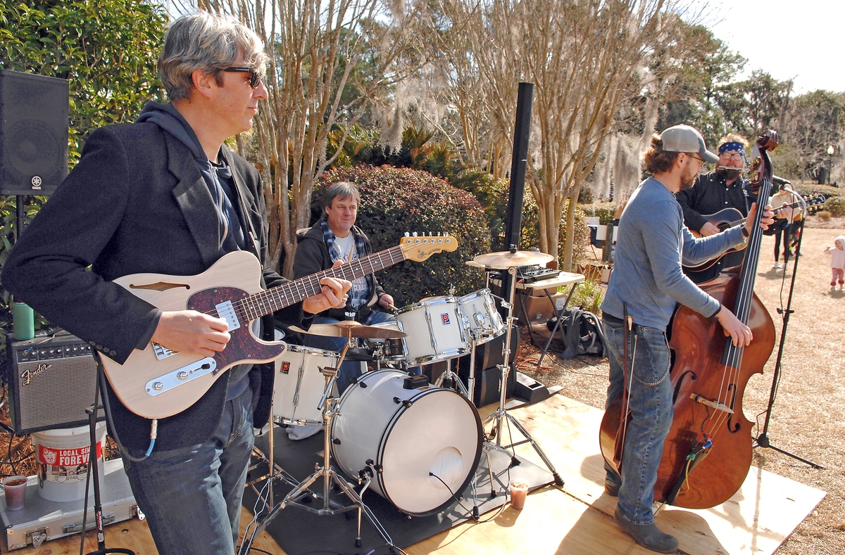 """Lead guitarist Tim Devine, left, of the Machete Flats Blues Quartet picks a tune while the rest of the band — Steve Aldred, drums; Adam """"Sushi"""" Graynade, bass; and Kirk Dempsey, guitar — joins in."""