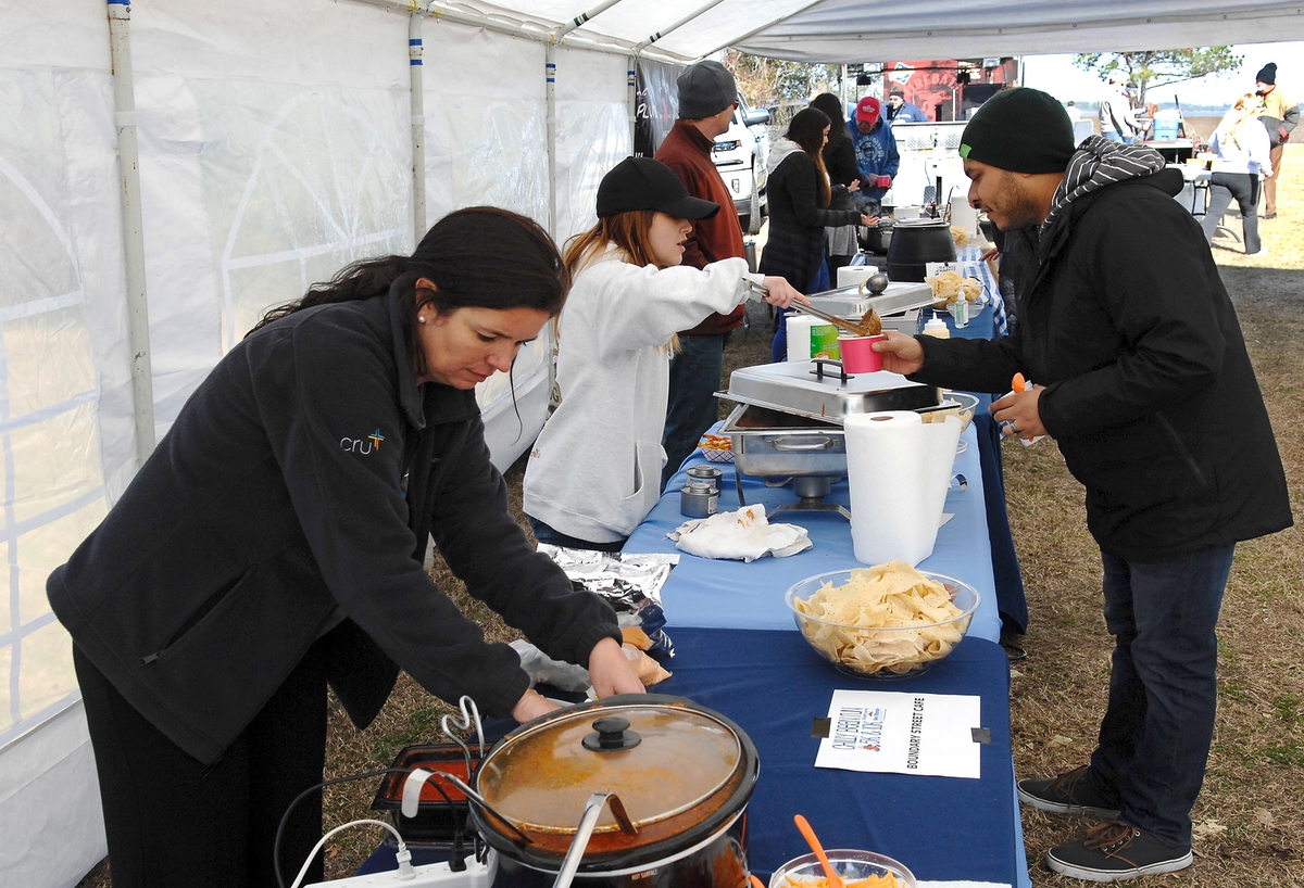 It wouldn't be a Chili Bean Cookoff without the chili. Here, Ozzy Quintanilla, gets a sample of from volunteer Ashley Lyda while Tammy Gates, left, cleans up a spill.