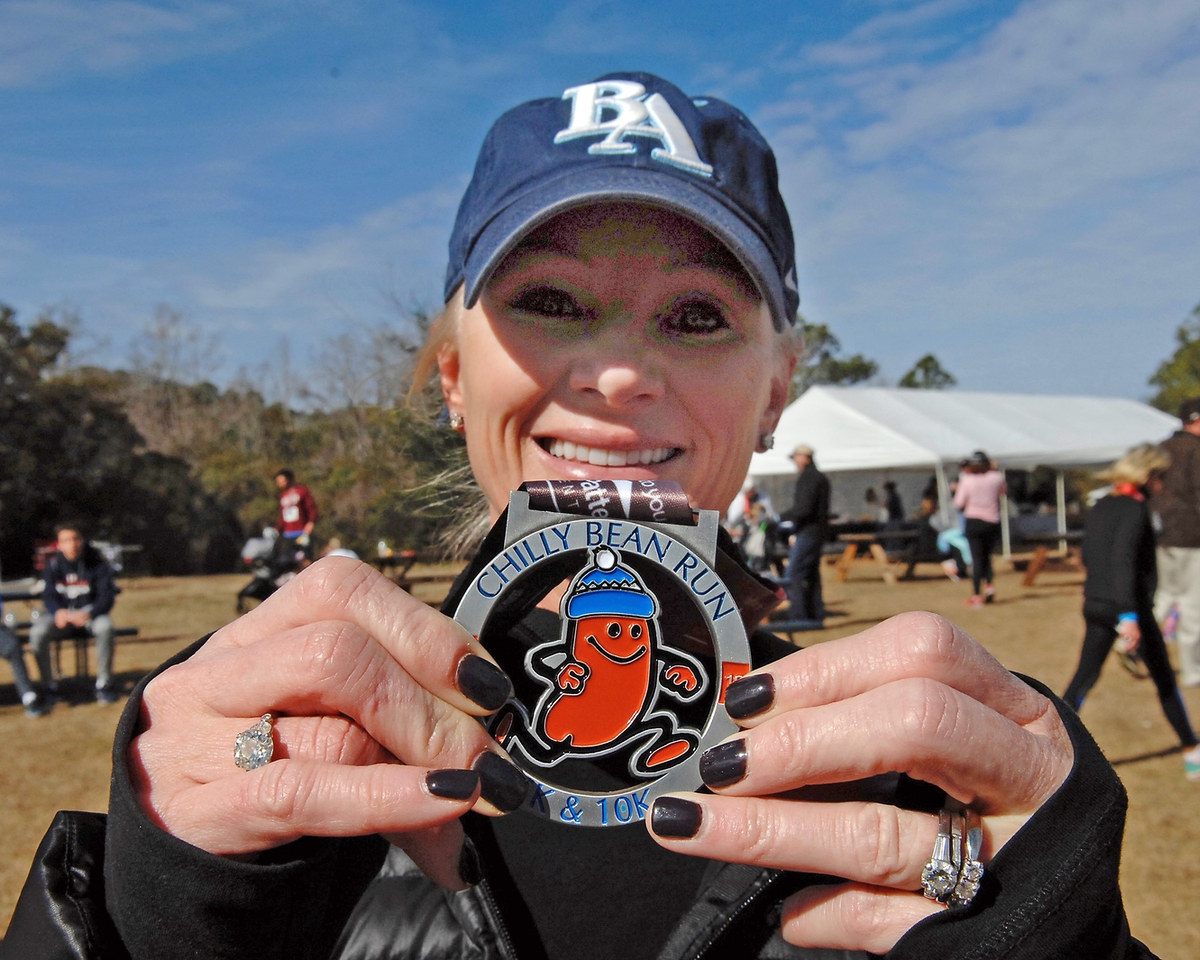Michelle Hiers proudly displays her participation medal for finishing the run. Hiers said she completed her 5K run in 33 minutes.