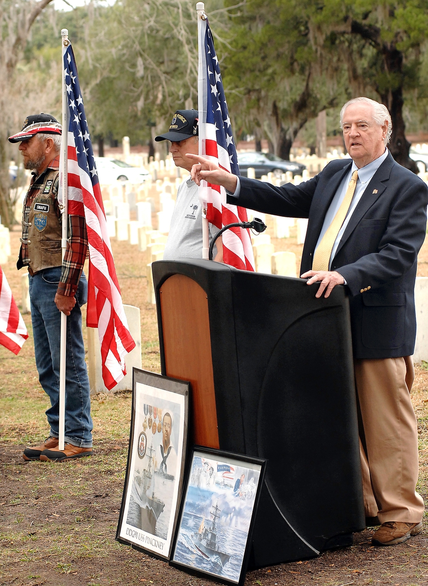 Flanked by members of the Patriot Guard Riders, local historian Larry Rowland describes his involvement in getting a new headstone for WWII veteran William Pinckney.